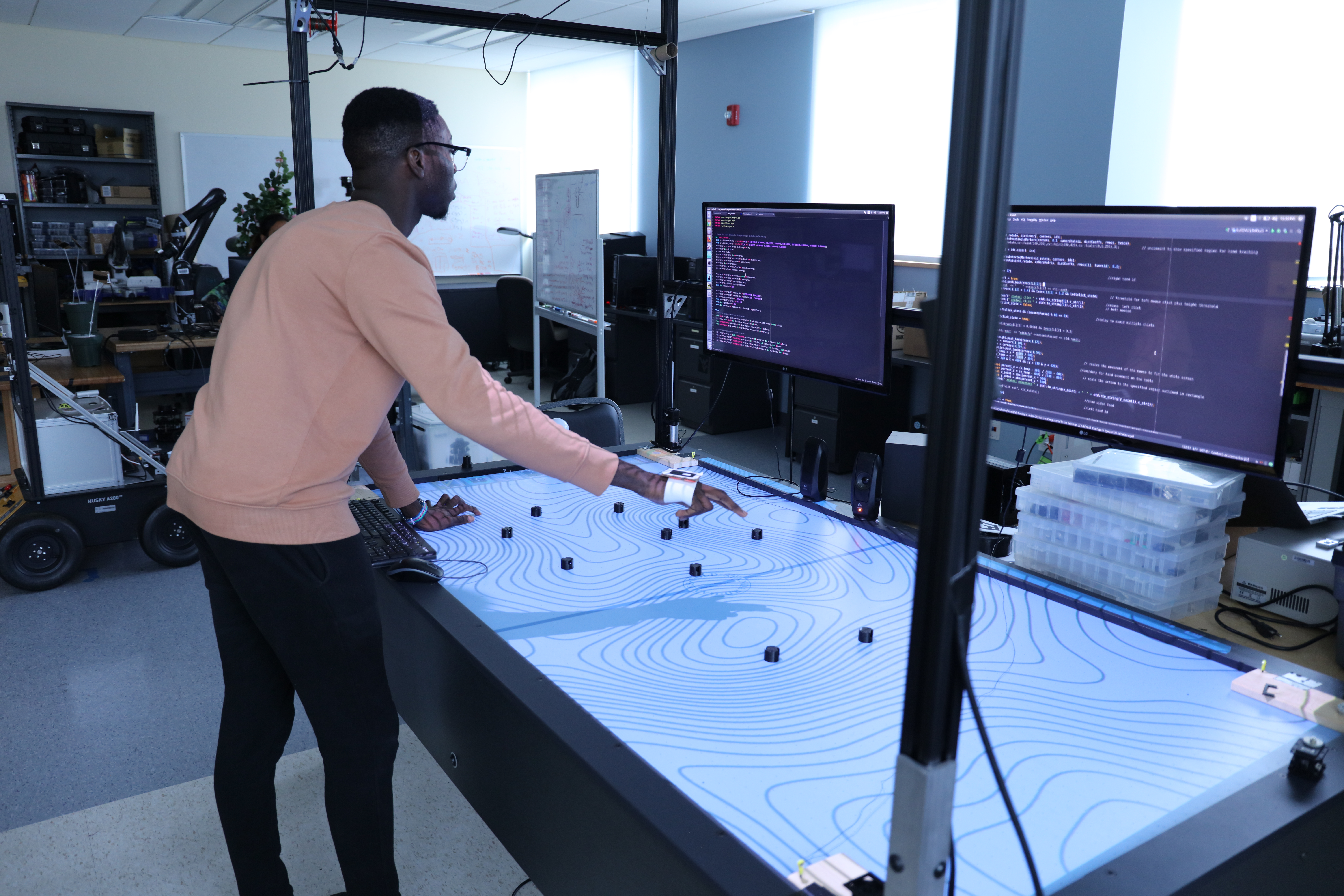 A tall man looks at a computer screen and an interactive whiteboard